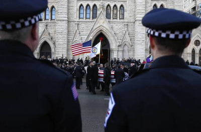 Officers salute as the body of Estrada is taken into Holy Name Cathedral in Chicago