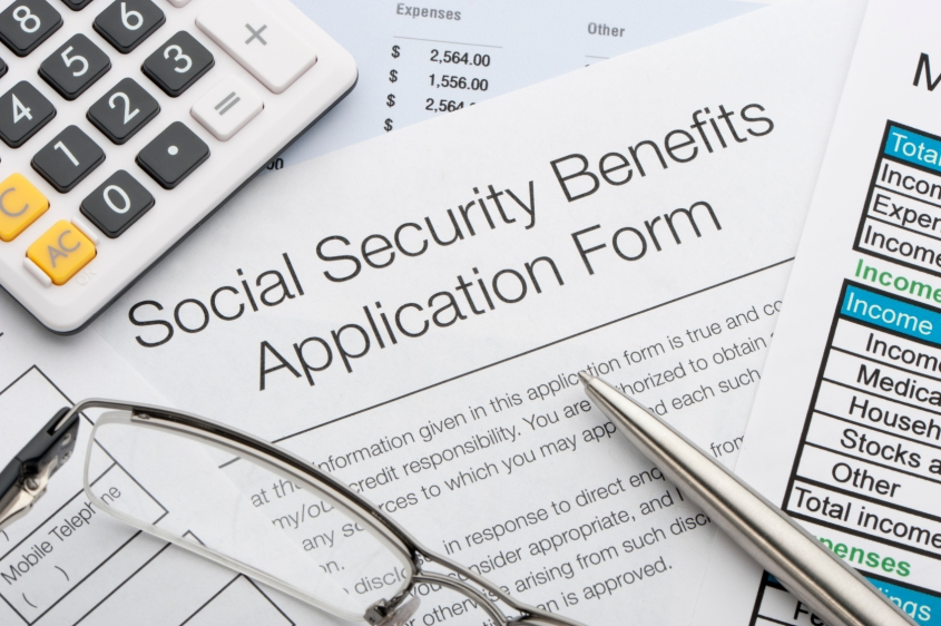 Close up of social security application with calculator and pen