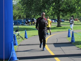 Maywood 5K man crossing finish line